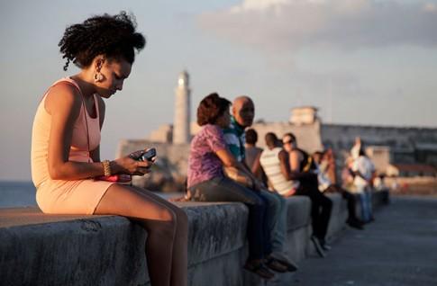 """Mulher usa celular no """"Malecón"""" de Havana. Apresentado como serviço comercial, """"twitter cubano"""" era controlado por agência norte-americana"""