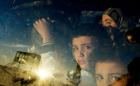 Crianças sírias cruzam, num carro, fronteira para Líbano. Possível ataque dos EUA só tornará aindaa pior uma guerra dramática